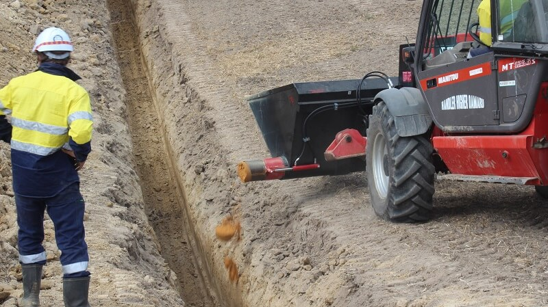 Rata Auger Bucket on Telehandler laying sand in a trench