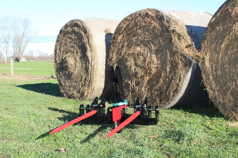 Rata Equipment Drawbar Hitch Bale Fork combo with tines down in front of hay bales