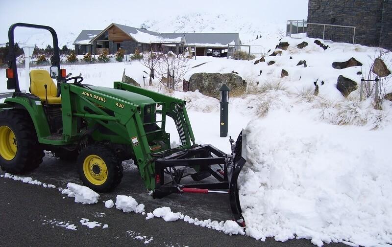 Mini snow plough on compact john deere loader in Tekapo