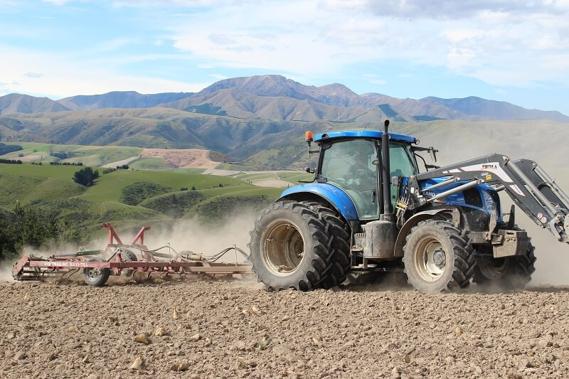 Rata 812 Trailing Maxitill cultivating stony ground behind New Holland Tractor
