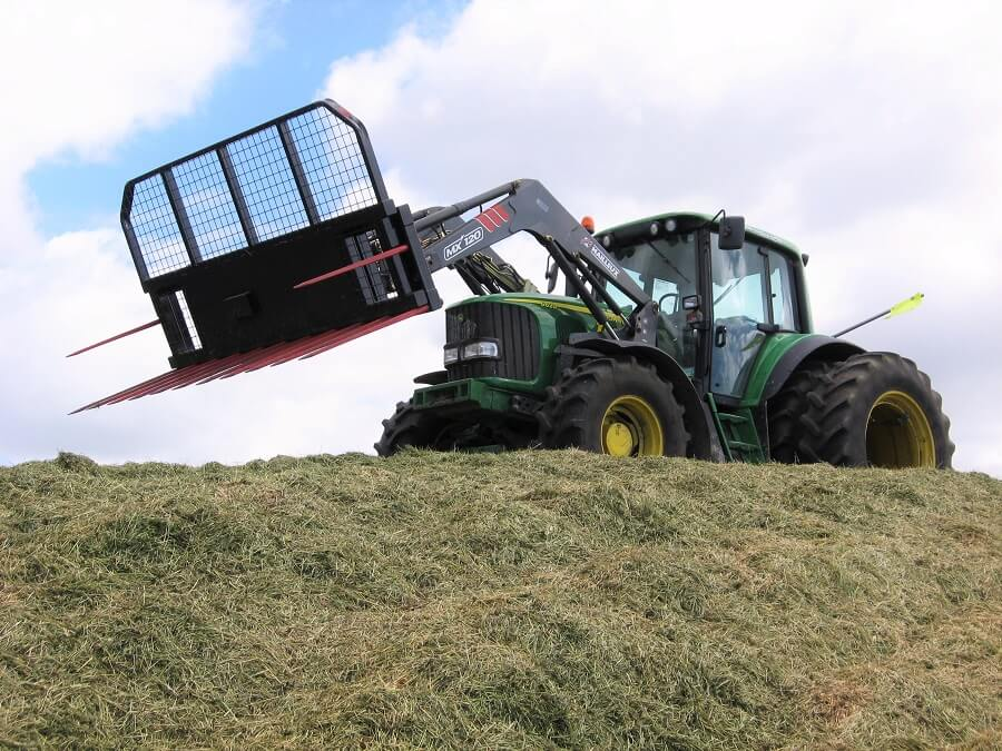 John Deere tractor making a silage stack
